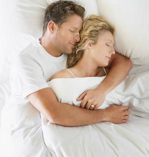 A man sleeping comfortably with his arms around a woman while he wears a Breathe Right Nasal Strip.