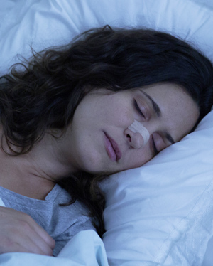 Woman sleeping comfortably with a Breathe Right nasal strip across her nose.
